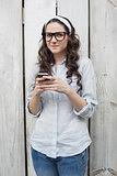 Pensive trendy woman with stylish glasses sending text message