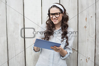 Smiling trendy woman with stylish glasses using her tablet