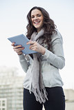 Cheerful pretty brunette holding her tablet pc