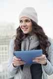 Cheerful pretty brunette holding her tablet