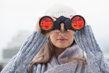 Cute woman with winter clothes on looking through binoculars