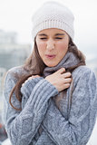 Shivering cute woman with winter clothes on posing