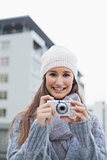 Cheerful gorgeous woman with winter clothes on taking picture