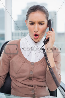 Angry businesswoman picking up the phone