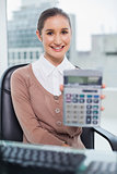Cheerful businesswoman showing her calculator to camera