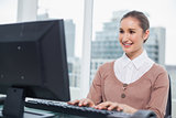 Smiling gorgeous businesswoman working on her computer
