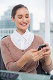 Smiling beautiful businesswoman text messaging