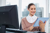 Cheerful beautiful businesswoman using her tablet