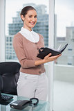 Happy beautiful businesswoman holding notebook