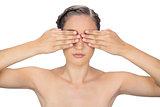Unsmiling woman hiding her eyes