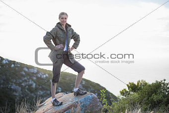 Woman standing on stone with hands on hips
