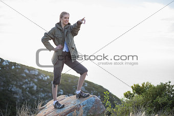 Smiling woman standing on stone