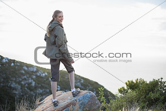Rear view of woman standing on stone looking back