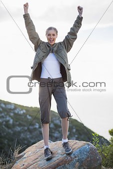Cheering woman standing on a rock