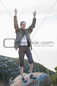 Blonde woman standing on a rock and cheering