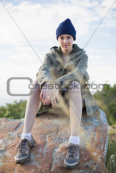 Woman wearing cap sitting on stone