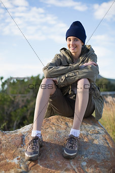 Smiling woman wearing cap sitting on a rock