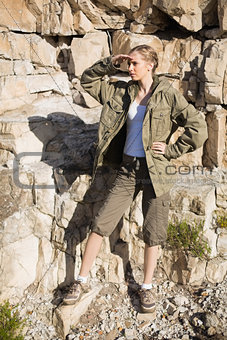Blonde woman hiking by a large rock face