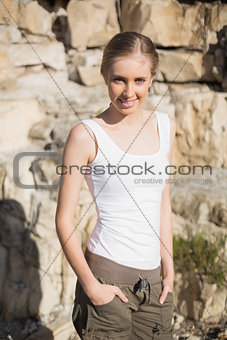 Smiling woman with hands in pants