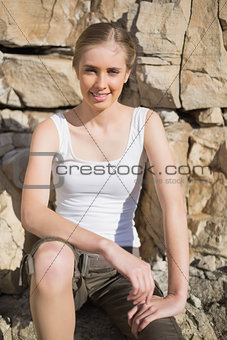 Woman sitting on stone with hands on leg