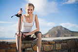 Woman holding hiking stick sitting on wall