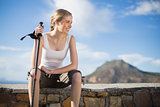 Woman sitting on wall holding hiking stick