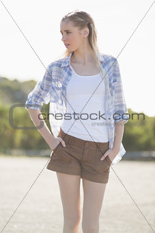 Blonde woman posing with hands in pockets