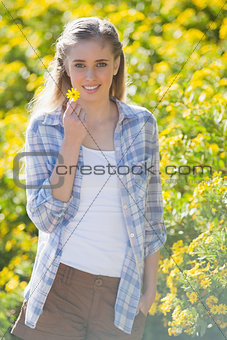 Blonde woman holding flower and smiling at camera