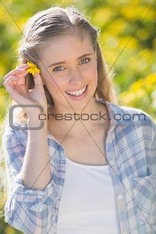 Blonde woman putting flower in hair