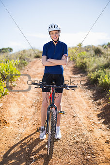 Smiling woman with bike crossing arms