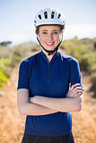 Smiling woman wearing helmet crossing arms
