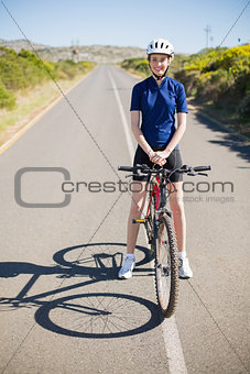 Smiling woman with bike on highway