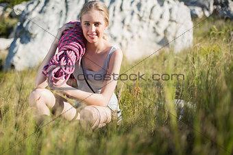 Blonde woman holding climbing equipment crouching down
