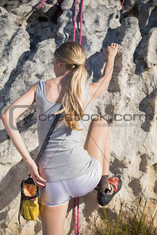 Blonde woman rock climbing