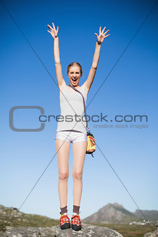 Active woman standing on rock cheering