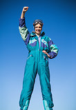 Smiling woman in ski suit putting hand up