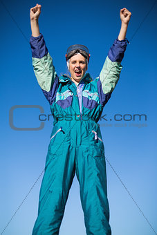 Woman wearing ski suit cheering