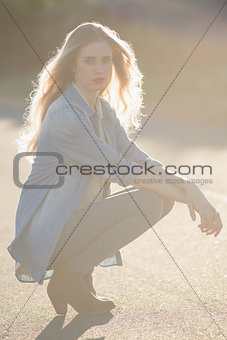 Blonde woman crouching down on a highway