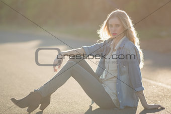 Attractive woman sitting on road