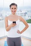 Smiling sporty brunette text messaging