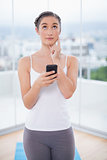 Thoughtful sporty brunette text messaging