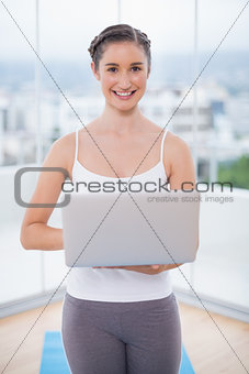 Cheerful sporty brunette using her laptop