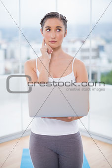 Thoughtful sporty brunette using her laptop