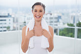 Smiling sporty brunette with white towel on shoulders