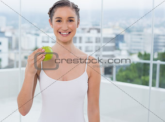Smiling sporty brunette holding green apple