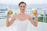 Cheerful sporty brunette holding apple and orange