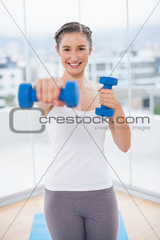 Smiling athletic brunette exercising with dumbbells
