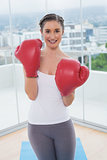 Smiling sporty brunette wearing red boxing gloves