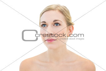 Pensive young blonde woman looking away