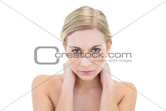 Irritated young blonde woman looking at camera